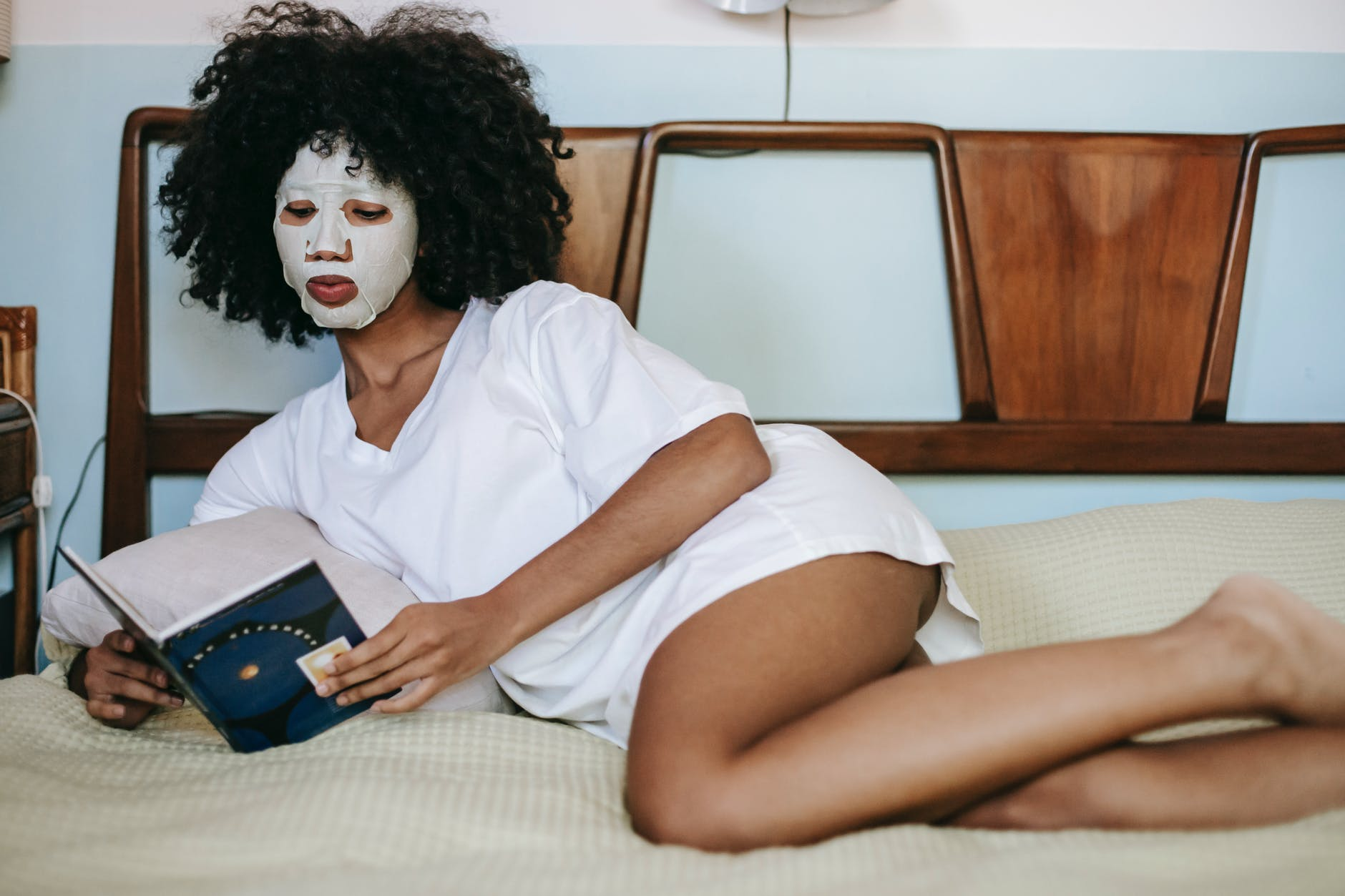 young woman lying on bed and reading book with cosmetic mask on face